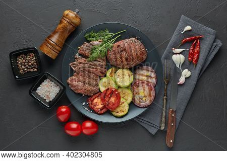 Roasted meat. Grilled beef steak and vegetables with spices on gray slate  background. Setting table. Steak menu. Grilled menu. Top view