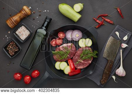 Raw fresh meat and vegetables. Beef steaks and cutting vegetables on grill  pan, olive oil and spices on black slate background. Top view. Steak menu
