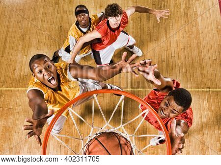 High angle shot of basketball player dunking basketball in hoop