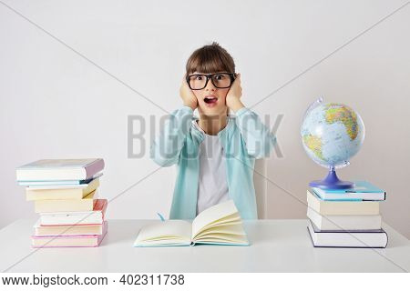 Pretty stylish schoolgirl learning using books and globe. elementary education concept. primary school