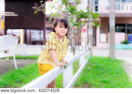 Little Girl In A Yellow Dress Stood By The White Fence. Child Pretended To Be Climbing The Fence To