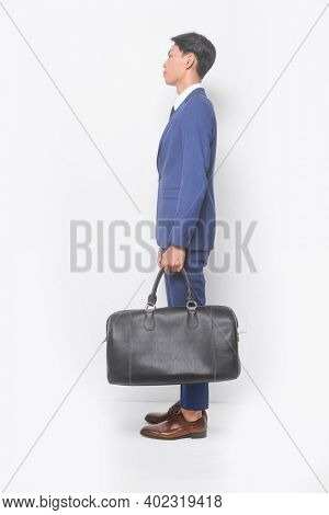 Side view full body young businessman  wearing blue suit ,tie with white shirt and blue pants ,holding black handbag with brown leather shoes