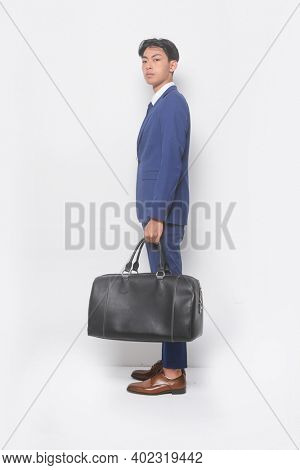 full body young businessman  wearing blue suit ,tie with white shirt and blue pants ,holding black handbag with brown leather shoes