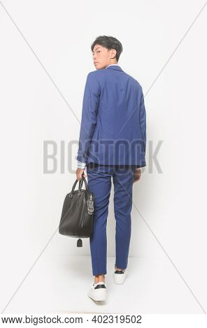 full body young businessman  wearing blue suit ,tie with white shirt and blue pants holding black handbag with sneakers shoes,back view