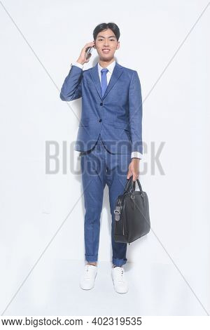 full body young businessman  wearing blue suit ,tie with white shirt and blue pants holding black handbag with cellphone sneakers shoes