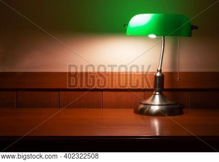 Vintage Lamp With Green Shade And Copy Space On Wooden Desk At Night