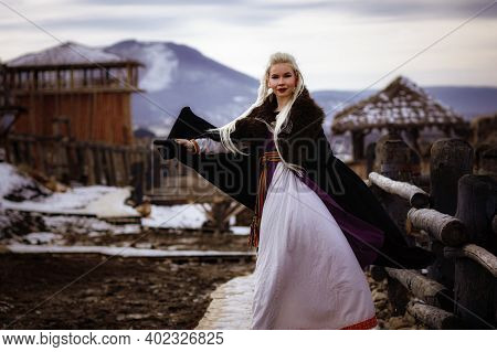 Beautiful Blonde Viking Dressed In A Black Cloak Against The Backdrop Of The Castle