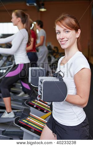 Happy woman near a crosstrainer lifting weights in a fitness center