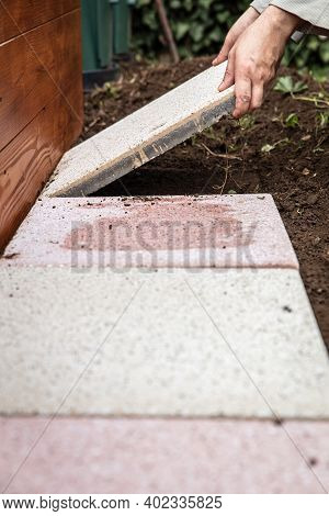 Man Is Laying Quadratic Tiles In The Garden, Building A Brick Path