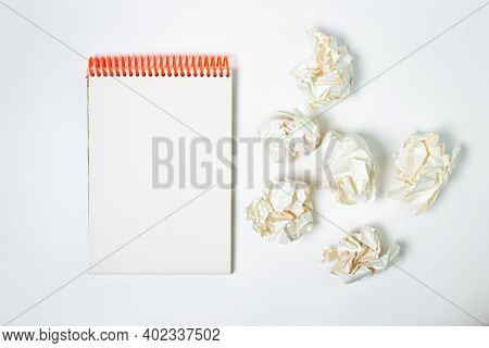 A Blank Sheet Of Notebook With Crumpled Paper Around. Crumpled Paper On A White Background. Creative