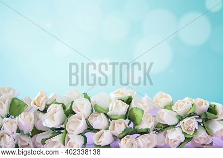 White Roses On Wooden Blue Background With Bokeh. Wedding Flowers And Bright Bokeh Glitter Backdrop.