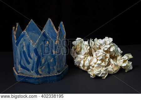 Cardboard Crown On A Black Background. Nearby Is A Pile Of Crumpled Paper. Paper Product. Fake Crown