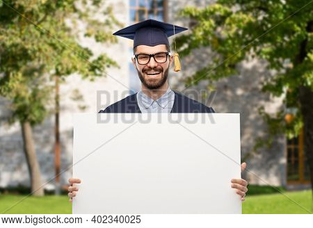 education, graduation and people concept - happy smiling male graduate student in mortar board and bachelor gown holding white board over university campus background