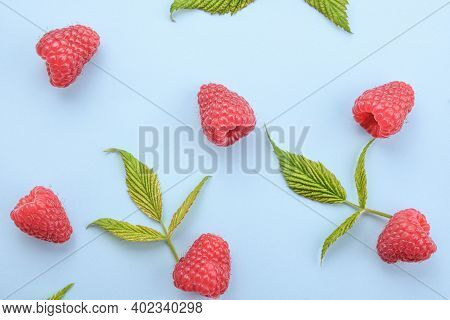 Pattern Of Raspberry And Green Leaves On Blue Background. Flat Lay Summer Berries - Red Raspberries.
