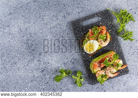 Healthy Snack Or Appetizer Toast With Salmon, Avocado, Shrimps, Eggs, Cucumber, Lambs Lettuce Or Cor