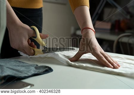 Womens Hands Cut Fabric On A Paper Pattern With Tailors Scissors On A White Table. A Dressmaker At W