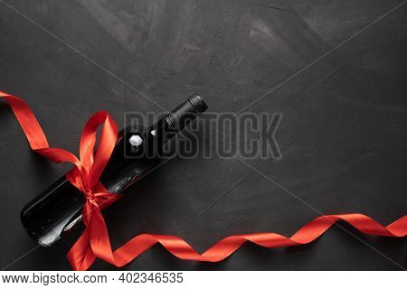 Wine Bottle With A Red Satin Ribbon Bow. Valentines Day. On A Concrete Background.