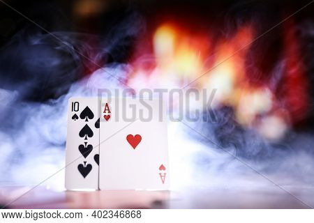 Poker Cards On A Table In A Smoke Against The Background Of A Fireplace. Online Gambling. Gamble Add