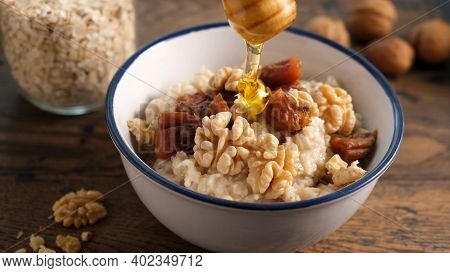 Oatmeal Porridge With Dried Fruits And Walnuts And Honey. Adding Honey To Healthy Breakfast Porridge