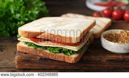 Sandwich With Ham, Cheese, Tomato And Lettuce On A Wooden Table. Tasty Healthy Sandwich
