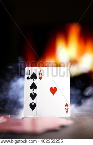A Pair Of Aces On A Deck Of Poker Cards In A Smoke Against The Background Of A Burning Fireplace. On