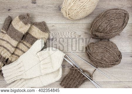Skeins Of Thread And Knitted Mittens On A Wooden Background. Mittens With A Flap. The Concept Of Hob