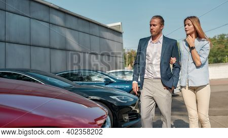 Happy Young Caucasian Pair Choosing New Car For Themselves While Walking Along Row Of Electric Autos