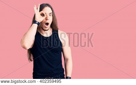 Young adult man with long hair wearing goth style with black clothes doing ok gesture shocked with surprised face, eye looking through fingers. unbelieving expression.