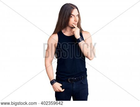 Young adult man with long hair wearing goth style with black clothes looking confident at the camera smiling with crossed arms and hand raised on chin. thinking positive.