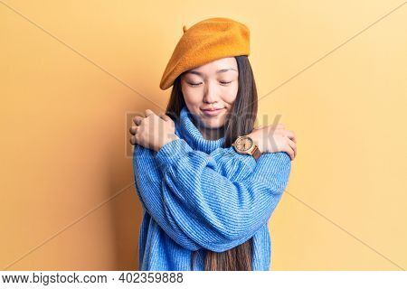 Young beautiful chinese woman wearing turtleneck sweater and french beret hugging oneself happy and positive, smiling confident. self love and self care