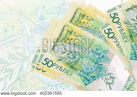 50 Belorussian Rubles Bills Lies In Stack On Background Of Big Semi-transparent Banknote. Abstract P