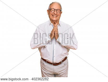 Senior caucasian man wearing business shirt and glasses praying with hands together asking for forgiveness smiling confident.