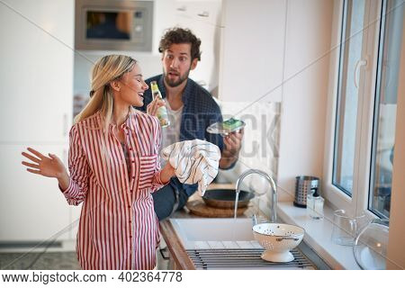 Young couple doing housework together in a cheerful atmosphere. Kitchen, housework, home, relationship