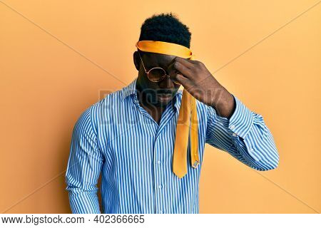 Handsome black man drunk wearing tie over head and sunglasses tired rubbing nose and eyes feeling fatigue and headache. stress and frustration concept.