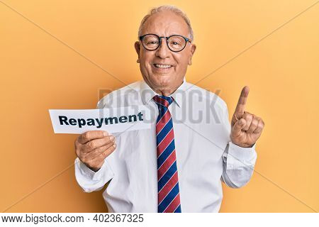 Senior caucasian man holding repayment word paper smiling with an idea or question pointing finger with happy face, number one
