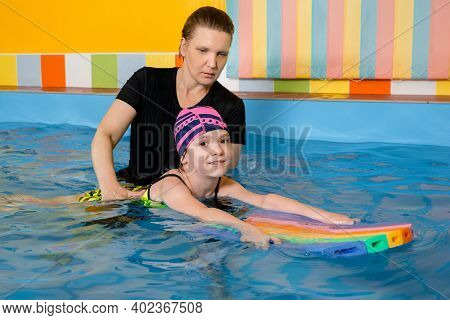 Coach Teaching Kid In Indoor Swimming Pool How To Swim With Flutter Board