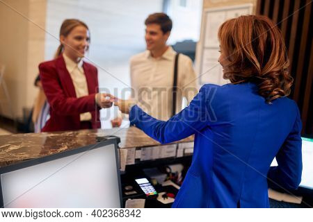 Young caucasian business couple checking in at hotel reception