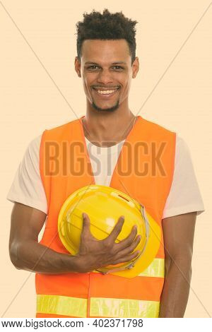 Young Happy African Man Construction Worker Smiling While Holding Safety Helmet Against Chest