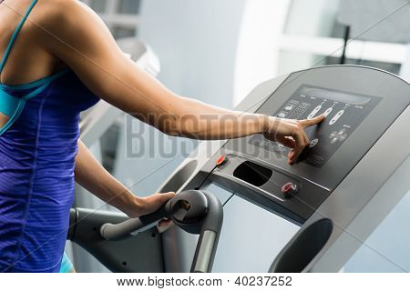 woman adjusts the treadmill