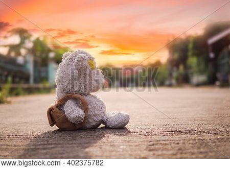 Broken Heart Concept. Alone Teddy Bear Sitting On Road With Sun Set. Conveys A Lonely Mood, Chagrin,