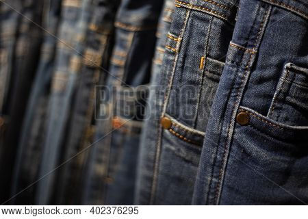 Closeup Many Jeans Hanging On A Rack. Row Of Pants Denim Jeans Hanging In Closet.