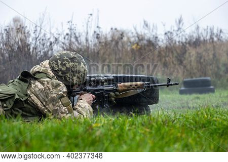 Sniper Operator In Camouflage Uniform And Body Armor Shoots From Dragunov's Sniper Rifle At The Firi