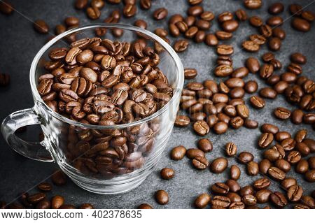 Coffee Mug Top View. Transparent Glass Cup Filled With Coffee Beans. Black Table Surface With Coffee
