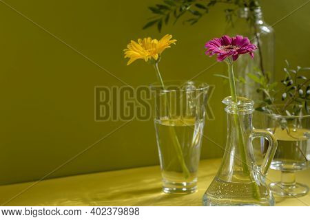 Beautiful Shadows From Glass Vases In Sunlight. Gerberas In Glass Bottles On A Yellow Background. A