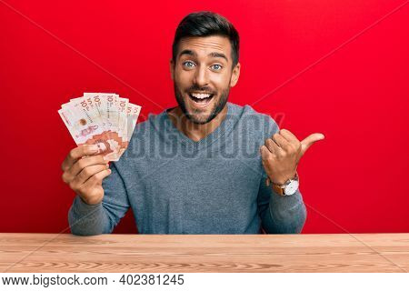 Handsome hispanic man holding colombian pesos pointing thumb up to the side smiling happy with open mouth