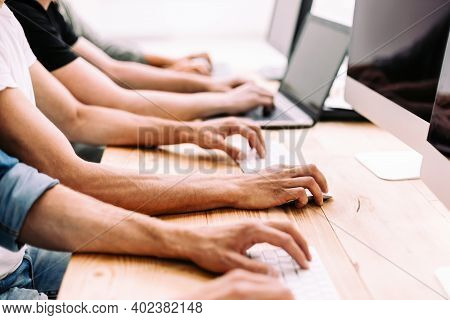 Close Up. A Group Of Employees Work On Their Computers