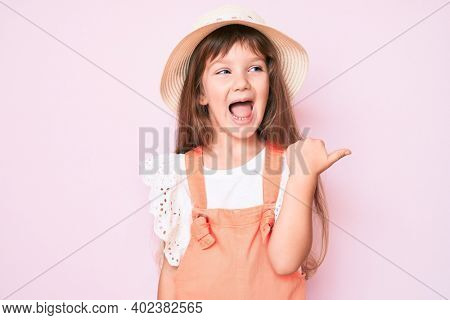 Little caucasian kid girl with long hair wearing spring hat pointing thumb up to the side smiling happy with open mouth