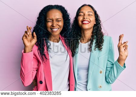 African american mother and daughter wearing business style gesturing finger crossed smiling with hope and eyes closed. luck and superstitious concept.