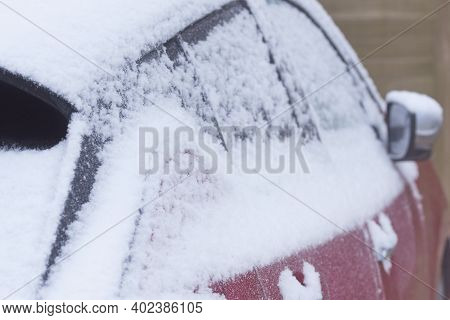 Snow On Sideof A Car Body Close Up At Snowy And Fogy Winter Day.