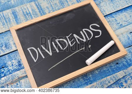 Dividends, Text Words Typography Written On Chalkboard Against Wooden Background, Life And Business
